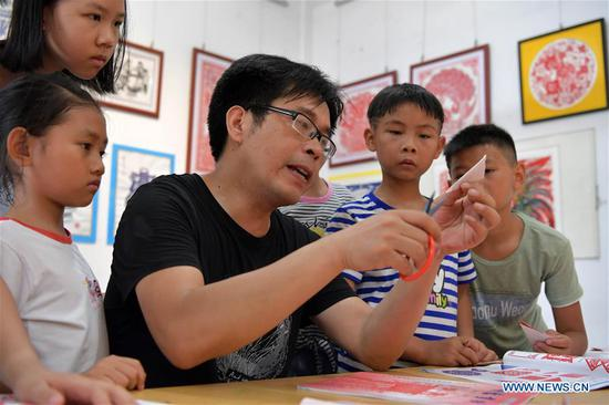 Peng Xuping, an inheritor of Xin'gan papercutting, guides children in papercutting in Xin'gan County, east China's Jiangxi Province, July 3, 2019. Xin'gan papercutting is listed as a national intangible cultural heritage. (Xinhua/Peng Zhaozhi) Peng Xuping, an inheritor of Xin'gan papercutting, guides children in papercutting in Xin'gan County, east China's Jiangxi Province, July 3, 2019. Xin'gan papercutting is listed as a national intangible cultural heritage. (Xinhua/Peng Zhaozhi)