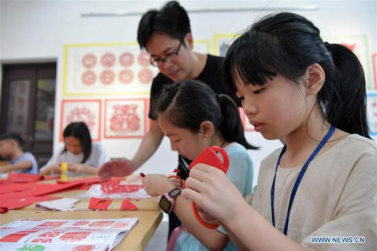 Peng Xuping, an inheritor of Xin'gan papercutting, guides children in papercutting in Xin'gan County, east China's Jiangxi Province, July 3, 2019. Xin'gan papercutting is listed as a national intangible cultural heritage. (Xinhua/Peng Zhaozhi)