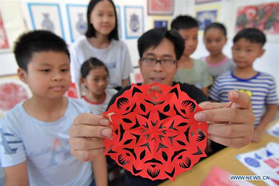 Peng Xuping, an inheritor of Xin'gan papercutting, shows a papercutting work in Xin'gan County, east China's Jiangxi Province, July 3, 2019. Xin'gan papercutting is listed as a national intangible cultural heritage. (Xinhua/Peng Zhaozhi)