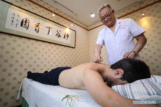 A guest experiences an acupuncture therapy during a traditional Chinese medicine tour on the sidelines of the Annual Meeting of the New Champions 2019, or Summer Davos, in Dalian, northeast China's Liaoning Province, July 3, 2019. (Xinhua/Pan Yulong)