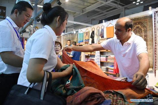 An Indian exhibitor introduces goods to guests during the Lanzhou Investment & Trade Fair in Lanzhou, capital of northwest China's Gansu Province, July 4, 2019. The fair opened here on Thursday, and will last for five days. (Xinhua/Chen Bin)