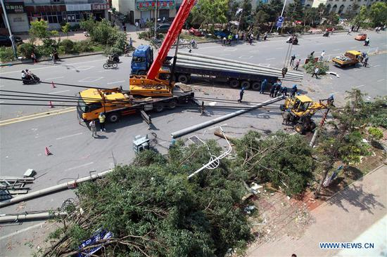 Rescuers clean the road and fix the power wires at a residential area impacted by tornado in Kaiyuan City, northeast China's Liaoning Province, July 4, 2019. An emergency medical expert team has rushed to Kaiyuan in northeast China's Liaoning Province to help with treating the injured following a deadly tornado Wednesday afternoon, the National Health Commission (NHC) said. The disaster left six people dead and over 190 others injured. Of the injured, 63 are still being treated at six hospitals, according to local authorities. (Xinhua)