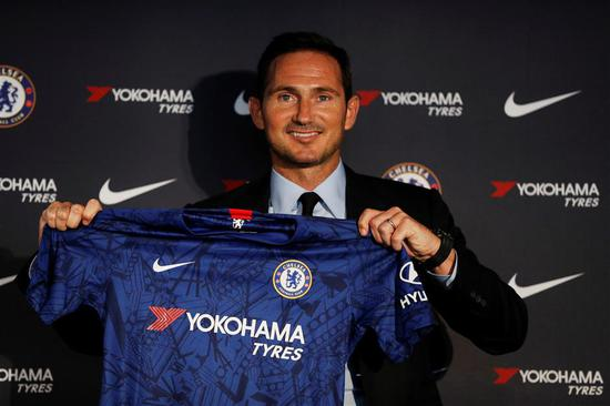 New Chelsea manager Frank Lampard holds up a club jersey during a press conference at Stamford Bridge, London, on Thursday.