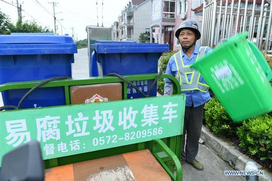 Ding Zhangliang, a perishable garbage sorter and deliverer, collects perishable garbage in Qianyuan Township of Deqing County, east China's Zhejiang Province, July 4, 2019. An all-rounded system dealing with garbage has been established in Deqing to sort, transport and dispose garbage. Collection rate of perishable garbage has been on steady growth. (Xinhua/Lin Shanchuan)