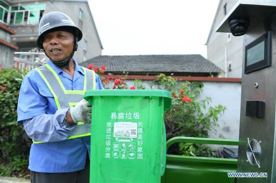 Ding Zhangliang, a perishable garbage sorter and deliverer, introduces a garbage can inserted with smart chips and a weighing machine uploading information on garbage sorting in Qianyuan Township of Deqing County, east China's Zhejiang Province, July 4, 2019. An all-rounded system dealing with garbage has been established in Deqing to sort, transport and dispose garbage. Collection rate of perishable garbage has been on steady growth. (Xinhua/Lin Shanchuan)