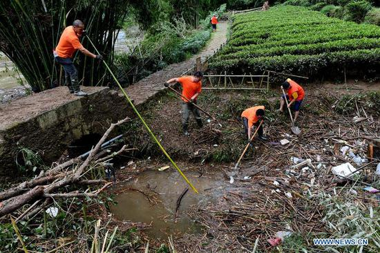 Staff members clean up garbages at the Mount Wuyi scenic area after a flood in southeast China's Fujian Province, July 10, 2019. Heavy rains hit Wuyishan City on Tuesday causing surge of water that damaged scenic spots and disrupted power and communications. (Xinhua/Zhang Guojun)