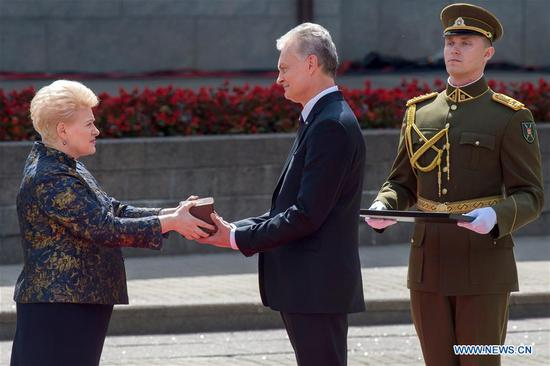 Lithuania's new President Gitanas Nauseda (C) and his predecessor Dalia Grybauskaite (L) attend a handover ceremony at the Presidential Palace in Vilnius, Lithuania, on July 12, 2019. Lithuania's new President Gitanas Nauseda on Friday started his term following his inauguration ceremony, pledging to tackle income and regional inequality, strengthen education and maintain the Euroatlantic integration. (Xinhua/Alfredas Pliadis)