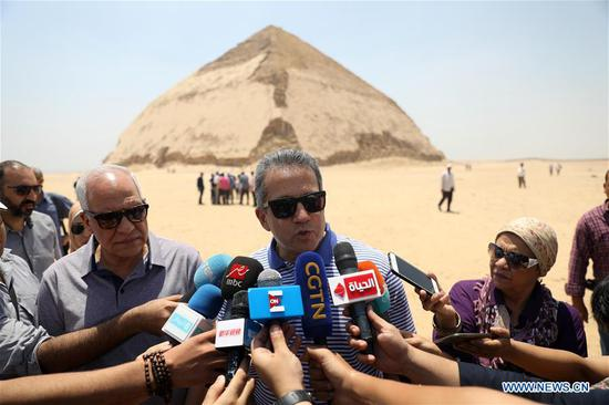 Egypt's Minister of Antiquities Khaled al-Anany (C) speaks during an interview in front of the Bent Pyramid in Giza, Egypt, on July 13, 2019. The Egyptian Ministry of Antiquities opened on Saturday the 4,600-year-old Bent Pyramid at Dahshur royal necropolis in Giza province southern the capital Cairo to visitors for the first time after its restoration and reparation works have been done. (Xinhua/Ahmed Gomaa)