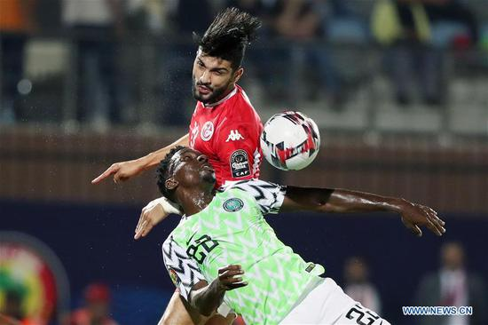 Kenneth Omeruo (Bottom) of Nigeria vies with Ferjani Sassi of Tunisia during the third place final at the 2019 Africa Cup of Nations in Cairo, Egypt, July 17, 2019. (Xinhua/Ahmed Gomaa)