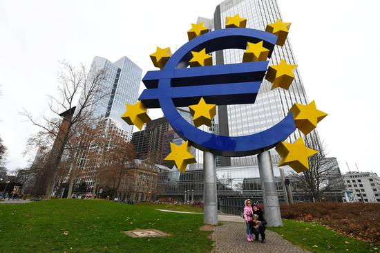 Photo taken on Dec. 30, 2018 shows the Euro sculpture in front of the Eurotower in Frankfurt, Germany. (Xinhua/Lu Yang)