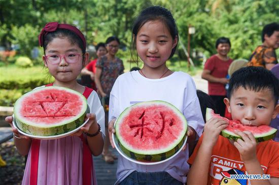 Children take part in a competition of eating watermelons to mark the upcoming