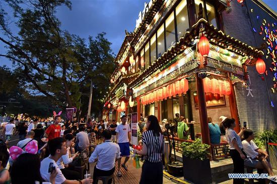 People wait outside a restaurant at Guijie, a lively gourmet restaurant street, at dusk in Beijing, capital of China, Aug. 7, 2019. (Xinhua/Li Xin)
