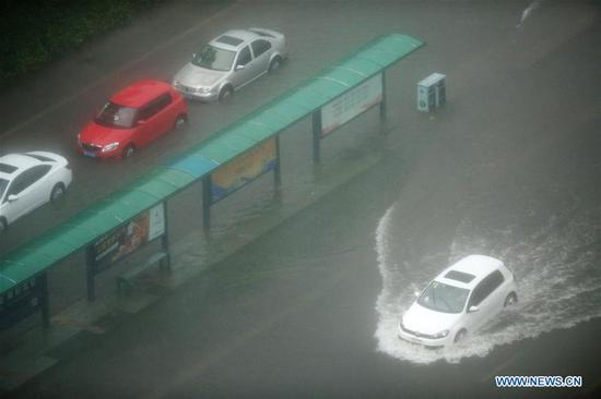 Cars run on a waterlogged street in Beilun District of Ningbo, east China's Zhejiang Province, Aug. 10, 2019. China's National Meteorological Center issued an orange alert for Typhoon Lekima on Saturday morning, as it landed in east China's Zhejiang Province. At around 1:45 a.m., the center of Typhoon Lekima, the ninth typhoon of the year, made landfall in the city of Wenling in Zhejiang, with a maximum wind force of 187 km/h. The super typhoon weakened to a typhoon at 5 a.m. at a maximum wind force of 144 km/h. (Xinhua/Weng Xinyang)