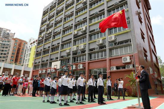 People attend a flag raising ceremony at a middle school in Yuen Long of New Territories, Hong Kong, south China, Aug. 11, 2019. The Association of Hong Kong Flag-guards held a flag raising ceremony at a middle school on Sunday. (Xinhua/Wu Xiaochu)