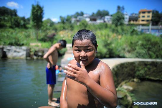 Children play in a pool in Shuitian Township of Wudang District in Guiyang, southwest China's Guizhou Province, Aug. 11, 2019. (Xinhua/Liu Xu)