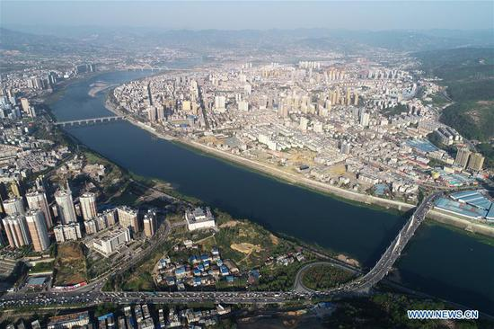 Aerial photo taken on April 7, 2019 shows a view of the Hanjiang River winding through the city of Ankang, northwest China's Shaanxi Province. In recent years, Ankang has been focusing on green development and seen rapid growth of eco-friendly industries. The city has also established some labor-intensive industries fabricating items as textile and toys, as a way to create jobs for low-income residents. (Xinhua/Shao Rui)