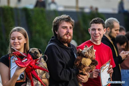 People and their dogs pose for a group photo during the Doggie Party in Moscow, Russia, on Aug. 11, 2019. Doggie Party, a competition for dogs, took place on Sunday in Moscow. (Photo by Maxim Chernavsky/Xinhua)