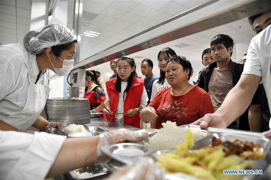People get meals at a middle school, which now serves as a relocation site, in Shouguang, east China's Shandong Province, Aug. 12, 2019. About 93,000 local residents have been relocated as Typhoon Lekima wreaked havoc in parts of Shouguang. (Xinhua/Guo Xulei)