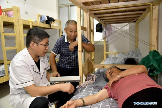 A resident receives medical treatment at a middle school, which now serves as a relocation site, in Shouguang, east China's Shandong Province, Aug. 12, 2019. About 93,000 local residents have been relocated as Typhoon Lekima wreaked havoc in parts of Shouguang. (Xinhua/Guo Xulei)