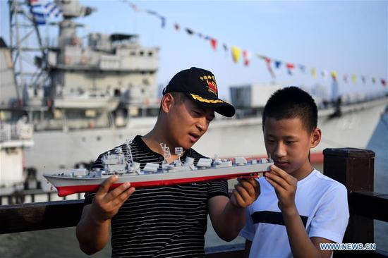 Yang Shuangfeng (L) holds a model of DDG-163 Nanchang, a decommisioned destroyer ship, when he introduces the ship to his son in Nanchang, east China's Jiangxi Province, Aug. 8, 2019. After it was decommissioned in September 2016, DDG-163 Nanchang, a Type 051 guided-missile destroyer of the People's Liberation Army (PLA) Navy, remains a tourist attraction in Nanchang, the city after which it was named. To navy veteran Yang Shuangfeng, the last Chief Engineer on DDG-163, the ship means more like a comrade than a mere tourist destination. When DDG-163 went out of service, Yang had realized that it was hard for him to just give up on this