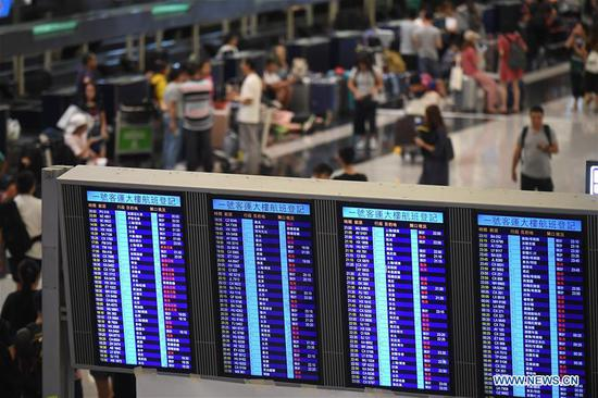 A screen displays flight status of the Hong Kong International Airport in Hong Kong, south China, Aug. 13, 2019. Protesters created chaos at the Hong Kong International Airport for the second day on Tuesday, causing cancellations of most outbound flights at one of the busiest airports in the world. (Xinhua/Lui Siu Wai)