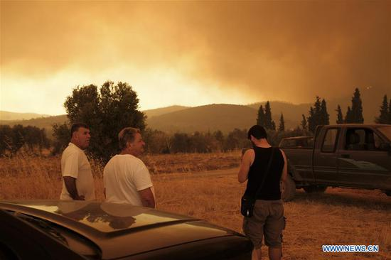 Local residents of Makrymalli look at a wildfire from a distance on Evia island, Greece, Aug. 13, 2019. Greek fire fighters were battling the largest wildfires of this summer raging in two major fronts near Athens on Tuesday, local authorities said. More than 500 residents have been evacuated from three villages as a precautionary measure and no injured have been reported neither near Thebes city in the mainland, northwest of the capital, nor on Evia island, two hour's drive from Athens, according to the Fire Service. (Photo by Nick Paleologos/Xinhua)