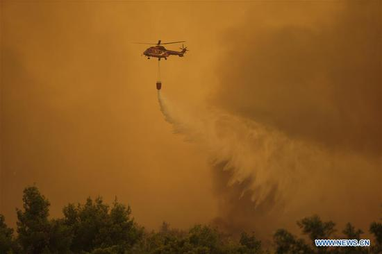 A water-dropping helicopter is seen battling a wildfire near Makrymalli village on Evia island, Greece, Aug. 13, 2019. Greek fire fighters were battling the largest wildfires of this summer raging in two major fronts near Athens on Tuesday, local authorities said. More than 500 residents have been evacuated from three villages as a precautionary measure and no injured have been reported neither near Thebes city in the mainland, northwest of the capital, nor on Evia island, two hour's drive from Athens, according to the Fire Service. (Photo by Nick Paleologos/Xinhua)