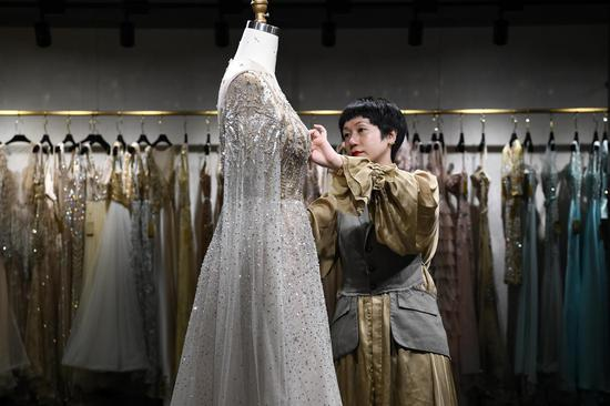 She Keyan, the official heir to the national heritage of Chao Embroidery, settles a wedding dress for display at a showroom for her personal brands in Chaozhou, south China's Guangdong Province, July 17, 2019. (Xinhua/Liang Xu)