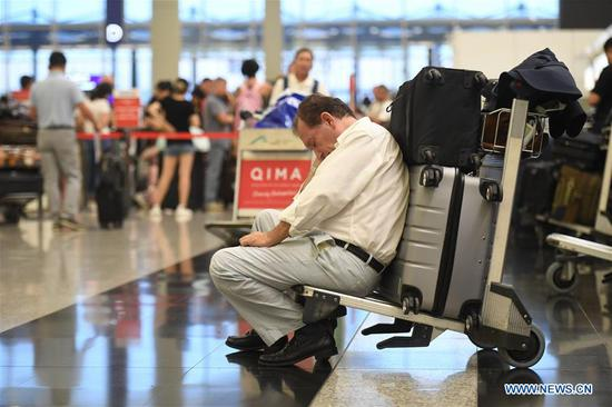 Tourists are stranded due to chaos caused by protesters at Hong Kong International Airport in Hong Kong, south China, Aug. 13, 2019. Protesters created chaos at the Hong Kong International Airport for the second day on Tuesday, causing cancellations of most outbound flights at one of the busiest airports in the world. (Xinhua/Lui Siu Wai)