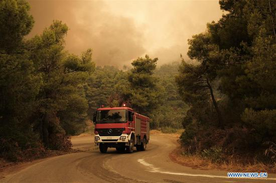 A fire engine is seen operating during efforts to extinguish a wildfire near Makrymalli village on Evia island, Greece, Aug. 13, 2019. Greek fire fighters were battling the largest wildfires of this summer raging in two major fronts near Athens on Tuesday, local authorities said. More than 500 residents have been evacuated from three villages as a precautionary measure and no injured have been reported neither near Thebes city in the mainland, northwest of the capital, nor on Evia island, two hour's drive from Athens, according to the Fire Service. (Photo by Nick Paleologos/Xinhua)