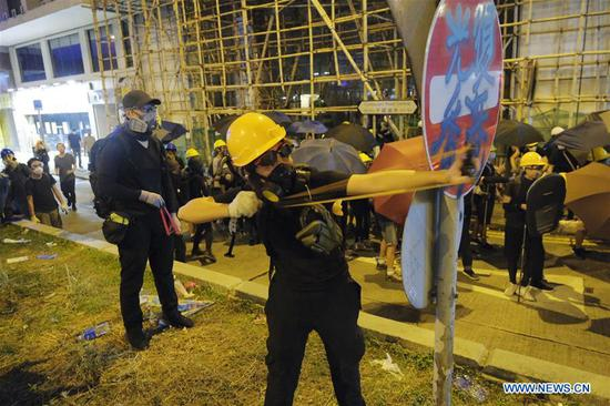 A violent radical attacks the police with a slingshot in Sheung Wan, south China's Hong Kong, July 28, 2019. Two months on, the escalating violence in Hong Kong has taken a heavy toll on the social order. Violent radicals committed acts of vandalism, blocked main traffic lanes, harassed urban commuters and set fires at will. Many have called for a brake to be put on the blatant violence and for order to be restored. (Xinhua)
