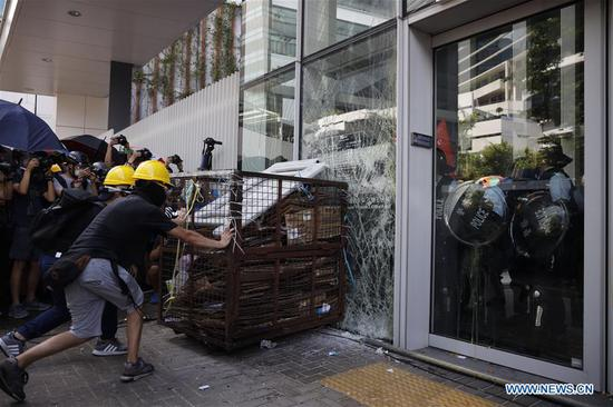 Violent radicals attempt to break and enter the Legislative Council building in Hong Kong, south China, July 1, 2019. Two months on, the escalating violence in Hong Kong has taken a heavy toll on the social order. Violent radicals committed acts of vandalism, blocked main traffic lanes, harassed urban commuters and set fires at will. Many have called for a brake to be put on the blatant violence and for order to be restored. (Xinhua)