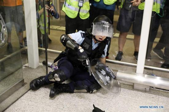A local police officer is knocked down by violent radicals in south China's Hong Kong, Aug. 13, 2019. Two months on, the escalating violence in Hong Kong has taken a heavy toll on the social order. Violent radicals committed acts of vandalism, blocked main traffic lanes, harassed urban commuters and set fires at will. Many have called for a brake to be put on the blatant violence and for order to be restored. (Xinhua)