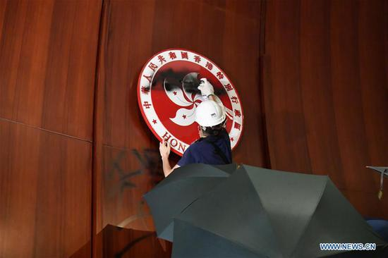 A violent radical vandalizes the regional emblem of Hong Kong Special Administrative Region after breaking and entering the Legislative Council building in Hong Kong, south China, July 1, 2019. Two months on, the escalating violence in Hong Kong has taken a heavy toll on the social order. Violent radicals committed acts of vandalism, blocked main traffic lanes, harassed urban commuters and set fires at will. Many have called for a brake to be put on the blatant violence and for order to be restored. (Xinhua)