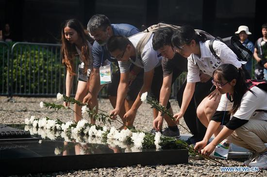 People mourn for Nanjing Massacre victims during a commemorative activity at the Memorial Hall of the Victims in Nanjing Massacre by Japanese Invaders in Nanjing, east China's Jiangsu Province, Aug. 15, 2019. A peace assembly was held Thursday in Nanjing, capital of east China's Jiangsu Province, to commemorate the 74th anniversary of Japan's surrender in World War II. A total of 20 representatives from Japan and over 140 youth representatives from ten countries including China, the Republic of Korea, the United States and the Philippines, attended the event held in the Memorial Hall of the Victims in Nanjing Massacre by Japanese Invaders, mourning the 300,000 people who were killed in one of the most barbaric episodes of World War II. (Xinhua/Ji Chunpeng)