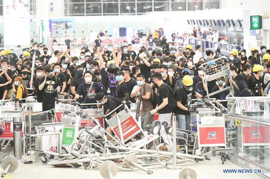 Violent radicals block a passage at Hong Kong International Airport in south China's Hong Kong, Aug. 13, 2019. Two months on, the escalating violence in Hong Kong has taken a heavy toll on the social order. Violent radicals committed acts of vandalism, blocked main traffic lanes, harassed urban commuters and set fires at will. Many have called for a brake to be put on the blatant violence and for order to be restored. (Xinhua)
