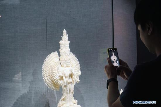 A visitor takes a picture of a porcelain statue displayed during an exhibition of Dehua porcelain held at Prince Kung's Mansion in Beijing, capital of China, Aug. 22, 2019. About 80 items of Dehua porcelain artworks made by artisans in southeast China's Fujian Province featuring Tibetan Buddhist statues in the Ming and Qing Dynasties (1368-1911) were on display during the ten-day exhibition, which kicked off here Thursday. Dehua porcelain is a type of white Chinese porcelain made in Dehua County of Fujian Province. Dehua is celebrated for its white porcelain, especially statues, such as those of Buddha. (Xinhua/Cui Bowen)