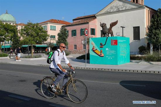 A man rides past a billboard for the 76th Venice International Film Festival in Venice Lido, Italy, on Aug. 27, 2019. The 76th Venice International Film Festival will kick off here on Wednesday. (Xinhua/Zhang Cheng)