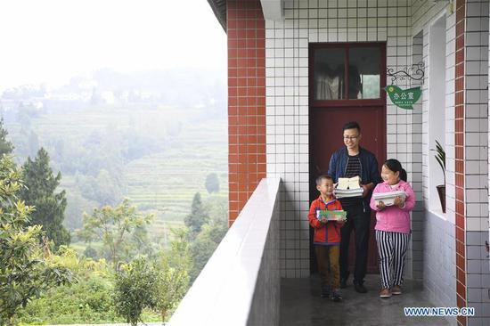 A teacher and two students carry books to the classroom at Shiliang Primary School in Dayou Township of Nanchuan District in southwest China's Chongqing, Sept. 2, 2019. Shiliang Primary School, composed of 2 teachers and 17 students, ushered in new semester on Monday. Tan Xingli and Liang Chengping are respectively in charge of the teaching work for 8 first graders and 9 pre-school students. Small-sized schools are boosted in recent years in the district to guarantee fair and quality education. (Xinhua/Wang Quanchao)