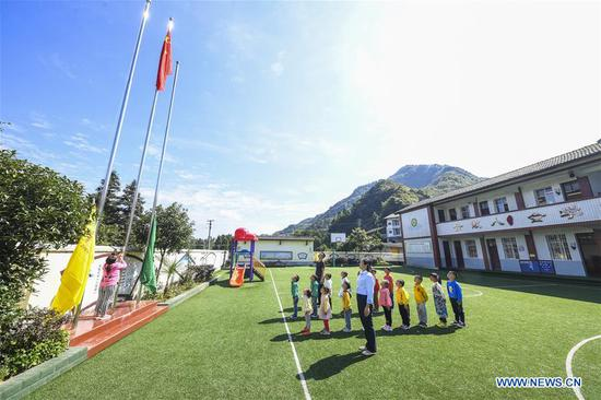 Teachers and students attend a flag-raising ceremony at Shiliang Primary School in Dayou Township of Nanchuan District in southwest China's Chongqing, Sept. 2, 2019. Shiliang Primary School, composed of 2 teachers and 17 students, ushered in new semester on Monday. Tan Xingli and Liang Chengping are respectively in charge of the teaching work for 8 first graders and 9 pre-school students. Small-sized schools are boosted in recent years in the district to guarantee fair and quality education. (Xinhua/Wang Quanchao)
