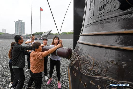 People strike the Bell of Peace at the Memorial Hall of the Victims in Nanjing Massacre by Japanese Invaders in Nanjing, east China's Jiangsu Province, Sept. 3, 2019. Activities were held Tuesday in Nanjing to commemorate the 74th anniversary of the victory in the Chinese People's War of Resistance Against Japanese Aggression and the World Anti-Fascist War. (Xinhua/Li Bo)