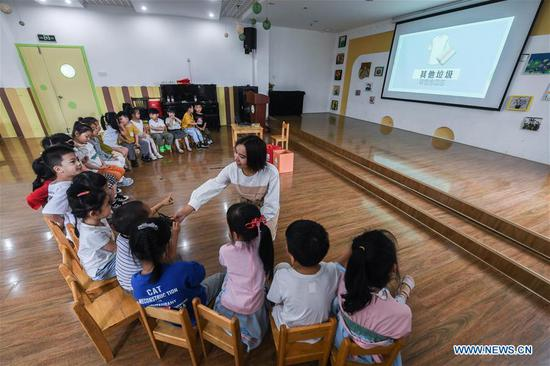A teacher gives a lecture on garbage sorting at a kindergarten in Huzhou, east China's Zhejiang Province, Sept. 4, 2019. Teachers of the kindergarten have organized various activities such as screening educational animations and playing fun games to help students learn the importance of garbage sorting as the new semester began. (Xinhua/Xu Yu)