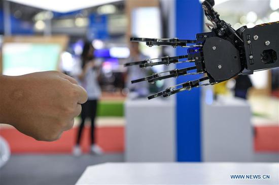 A visitor plays the finger-guessing game with a robot at an exhibition of high technologies and equipment during the fourth China-Arab States Expo in Yinchuan, northwest China's Ningxia Hui Autonomous Region, Sept. 7, 2019. The fourth China-Arab States Expo has helped promote cross-border high-tech exchange and cooperation. At an exhibition of high technologies and equipment held as part of the expo, visitors are exposed to major scientific and technological breakthroughs and state-of-the-art equipment developed by the high-tech sector. (Xinhua/Feng Kaihua)