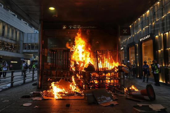 A fire set by protesters burns at the entrance of the Central MTR subway station in Hong Kong yesterday. Rioters descended onto the city's Central district, blocking roads and forcing the closure of an underground rail station.