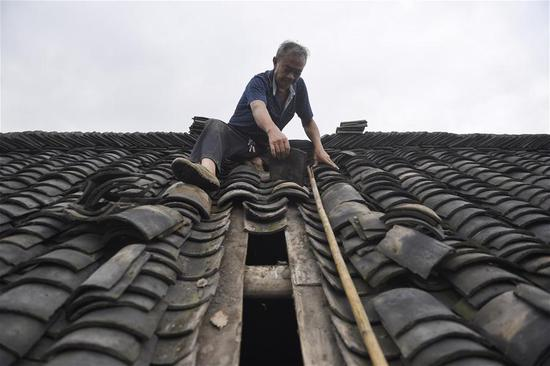 Villager Ni Xicai fixes the roof of a house at a village in Longhui Town of Weiyuan County, Neijiang City, southwest China's Sichuan Province, Sept. 8, 2019. The 5.4-magnitude earthquake in Sichuan Province had killed one person and left 63 others injured, three severely, as of 6 p.m. Sunday, local authorities said. (Xinhua/Liu Kun)