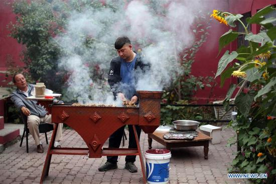 A local resident makes grilled lamb chops while attending a feast with neighbors in Tacheng, northwest China's Xinjiang Uygur Autonomous Region, Sept. 4, 2019. (Xinhua/Cheng Li)