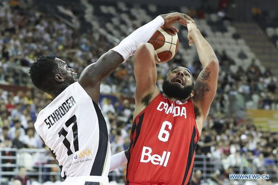 Cory Joseph (R) of Cananda goes up for the basket as Dennis Schroder of Germany blocks during the group P match between Germany and Canada at the 2019 FIBA World Cup in Shanghai, China, Sept. 9, 2019. (Xinhua/Ding Ting)
