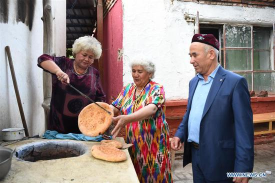 Local residents take 'Nang', a kind of crusty pancake, out of an oven while attending a feast in Tacheng, northwest China's Xinjiang Uygur Autonomous Region, Sept. 4, 2019. (Xinhua/Sadat)