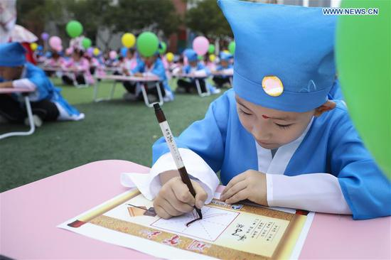 A student writes Chinese calligraphy during a first writing ceremony, a traditional education activity, at a school in Lanzhou, northwest China's Gansu Province, Sept. 10, 2019. (Photo by Ma Xiping/Xinhua)