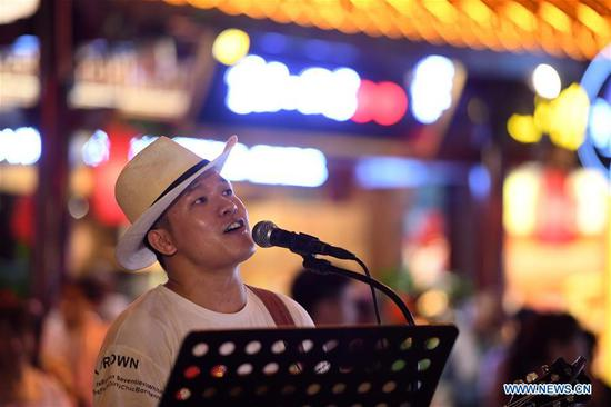 A singer performs in Hongyadong scenic spot at night in Yuzhong District, southwest China's Chongqing Municipality, Sept. 9, 2019. The development of nighttime economy in Chongqing enriches citizens' consumption choices and attracts visitors. Nighttime economy refers to business activities between 6 p.m. (1000 GMT) and 6 a.m. (2200 GMT) in the service sector. (Xinhua/Tang Yi)